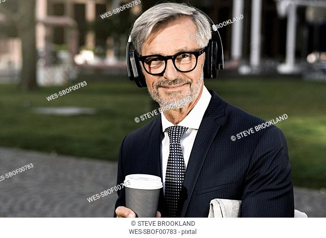 Grey-haired businessman with headphones and coffee to go looking into camera