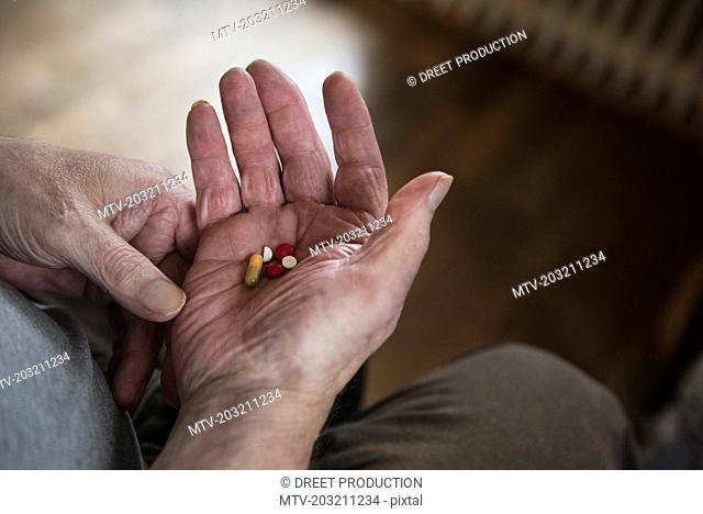 Close-up of senior man holding tablets in palm of hand