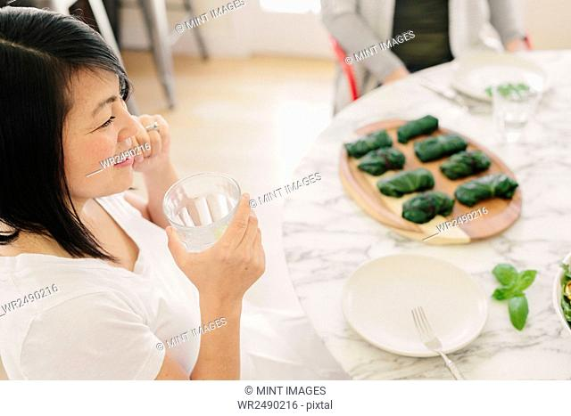 A woman seated at a table, by a plate of fresh dolmades