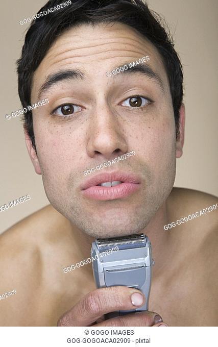 Man shaving with electric razor