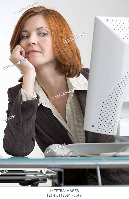 Businesswoman looking askance at her computer