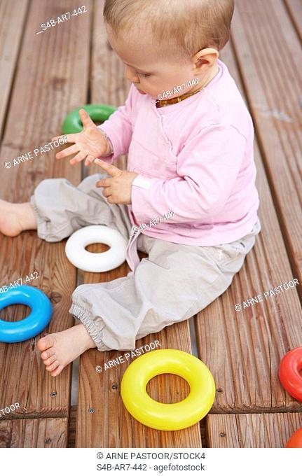Baby sitting on deck, Engen, Baden-Wuerttemberg, Germany