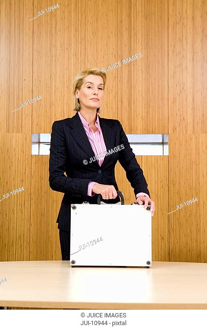 Businesswoman at conference table, hands on briefcase, portrait