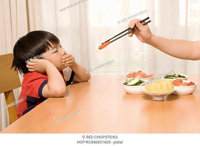 Person's hand holding chopsticks and feeding a boy