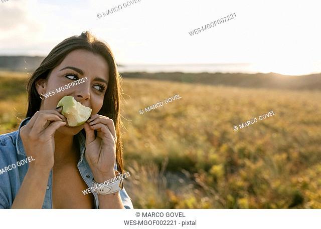 Spain, Asturias, beautiful young woman eating an apple