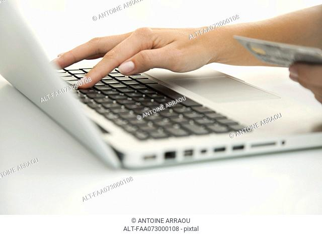 Woman using laptop computer to make an internet purchase, cropped