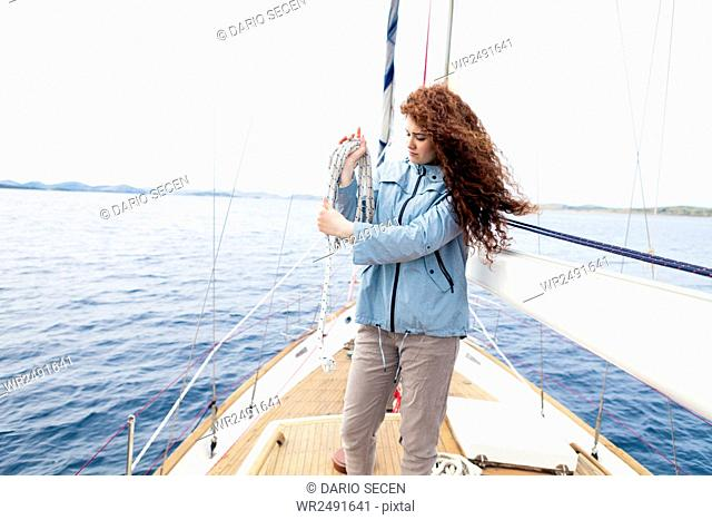 Young woman on yacht curling up rope
