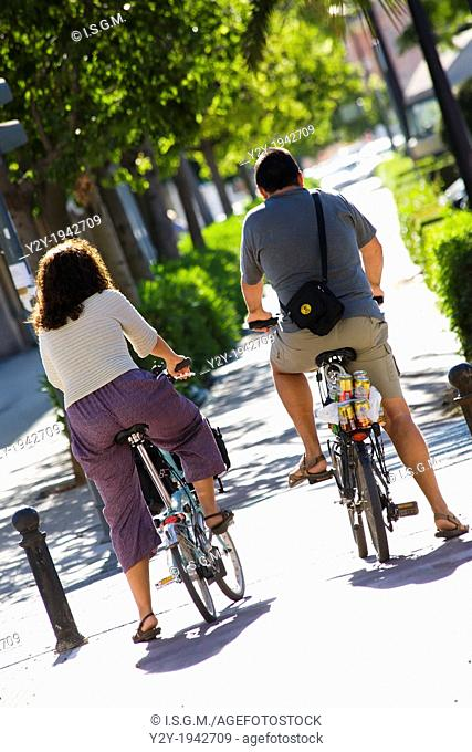 Couple of european people on bycicle. Valencia City, Spain