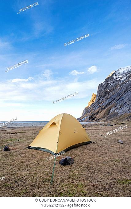 Tent pitched below mountains at Bunes beach, Moskenesøy, Lofoten Islands, Norway