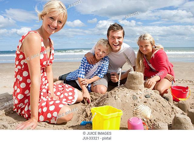 Portrait of smiling family making sandcastle on sunny beach