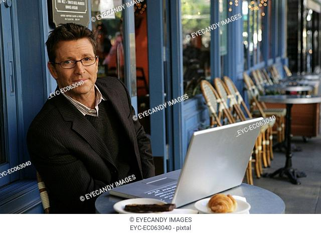 Mature man sitting at an outdoor cafe with a laptop