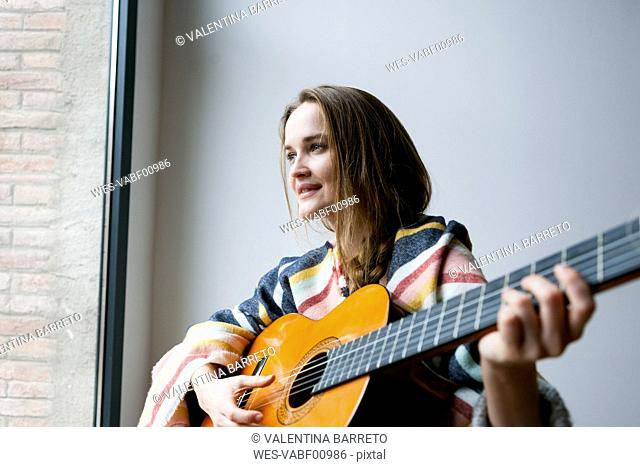 Young woman with blanket playing guitar