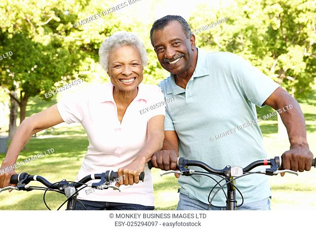 Senior African American Couple Cycling In Park
