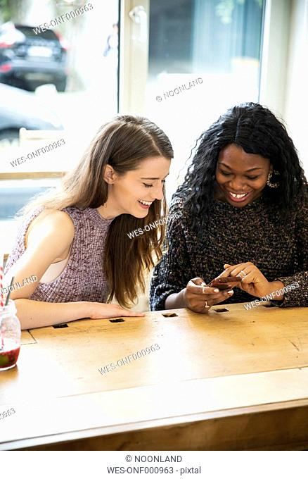 Two young woman using smart phone in cafe