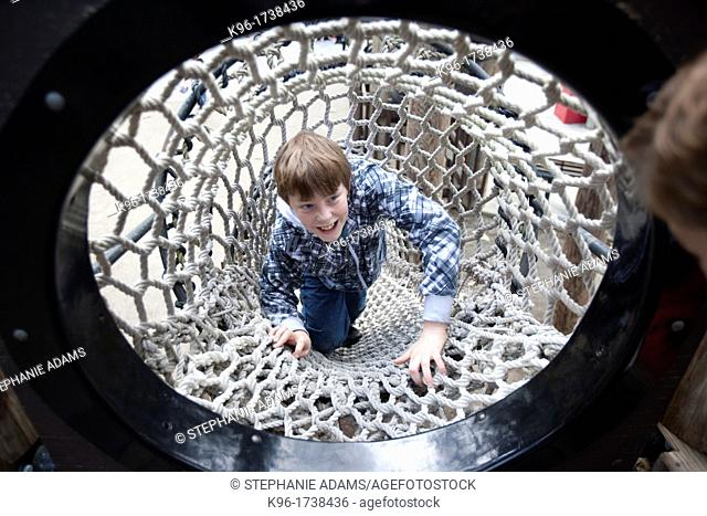 boy laughing while climbing a rope tunnel