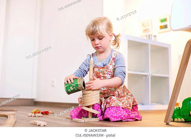 Girl kneeling on wooden floor playing with toys