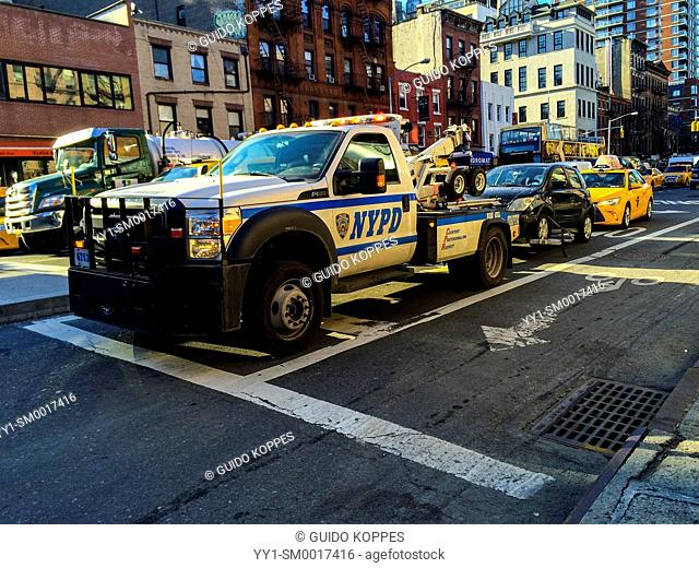 Manhattan, New York City, USA. A wrongly parked car is being towed away by the NYPD