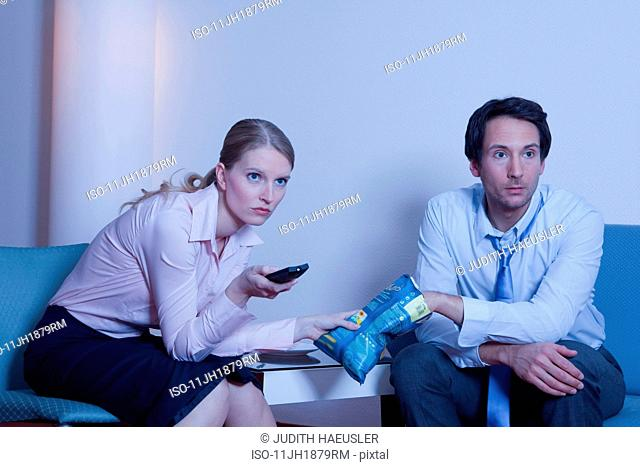 couple in hotel room, watching TV