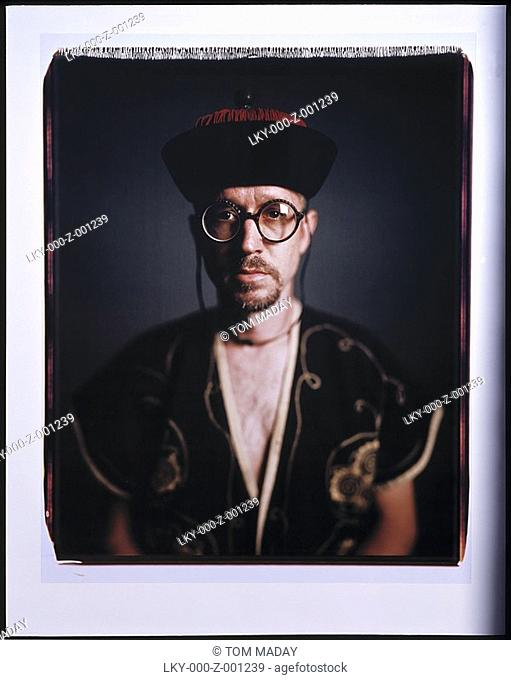 Studio portrait of man wearing large round glasses and Mandarin hat and top