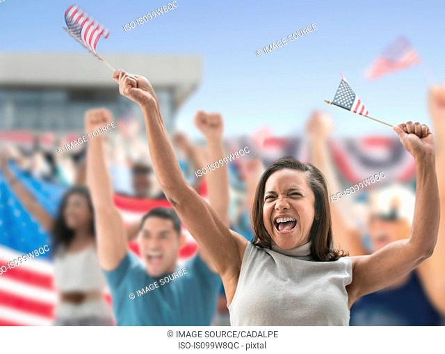 Excited woman waving american flags at rally