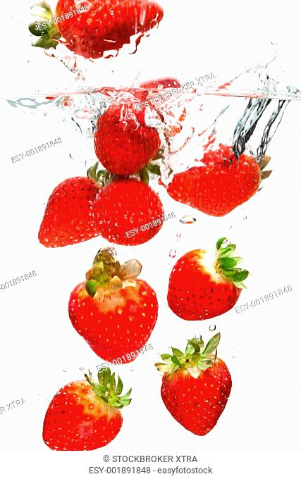 Photo of strawberries falling into water with motion blur shot against a white background