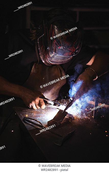 Blacksmith welding a piece of metal