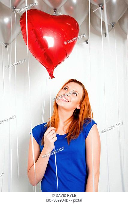 Young woman holding a heart shaped balloon