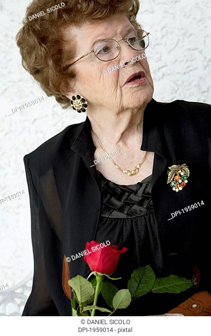 Portrait Of A Woman Holding A Single Red Rose; Edmonton, Alberta, Canada