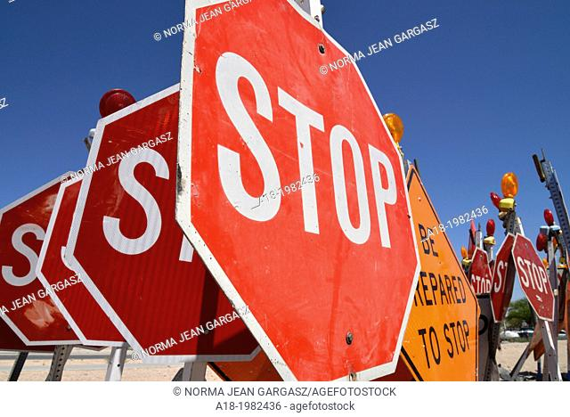 Traffic control signs await placement at a road construction site