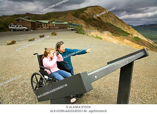 A mother reads an outdoor interpretive display panel with her daughter who is in a wheelchair at a handicap viewpoint Denali NP Alaska