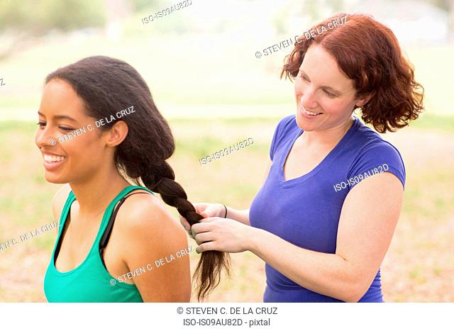 Young woman behind friend plaiting hair smiling