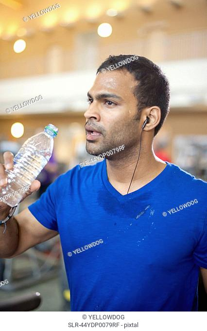 Man drinking water bottle in gym