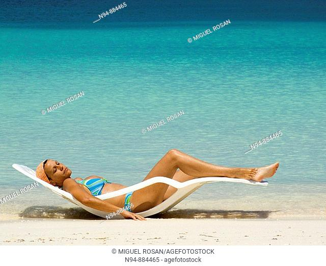 Girl in hammock taking sun bath on a Caribbean beach