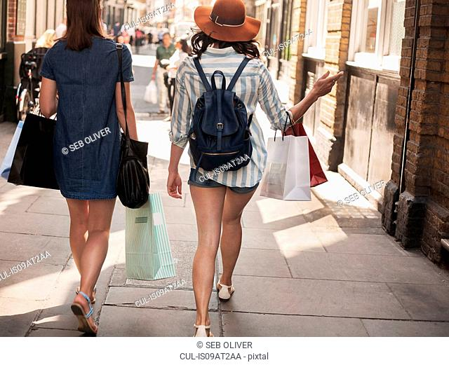 Rear view of two women carrying shopping bags on city street
