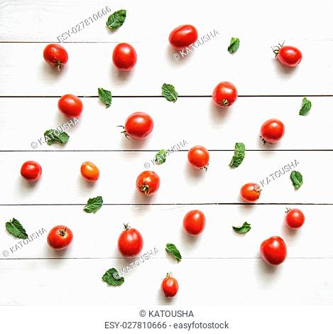 Tomatoes with basil leaves on white wooden table. Top view. Vegetable pattern