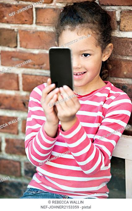 Young girl taking photo with smart phone