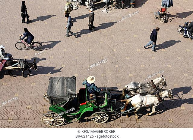 Horse-drawn carriage and pedestrians at Djemaa el-Fna, Marrakech, Morocco, Africa