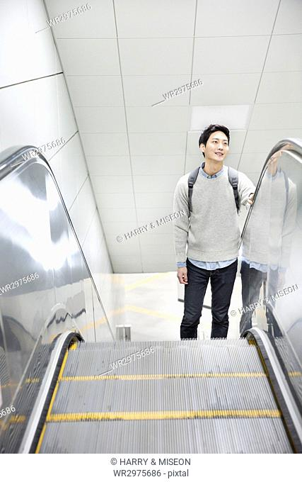 Young smiling man taking escalator up