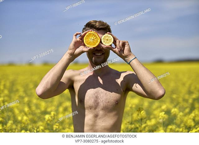 Shirtless man holding halved citrus fruit in front of eyes, standing in colza field