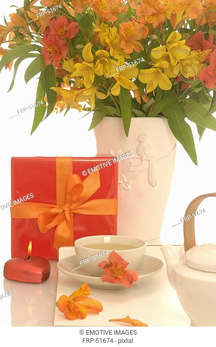 Arrangement of tea pot, a cup of tea, gift and bouquet