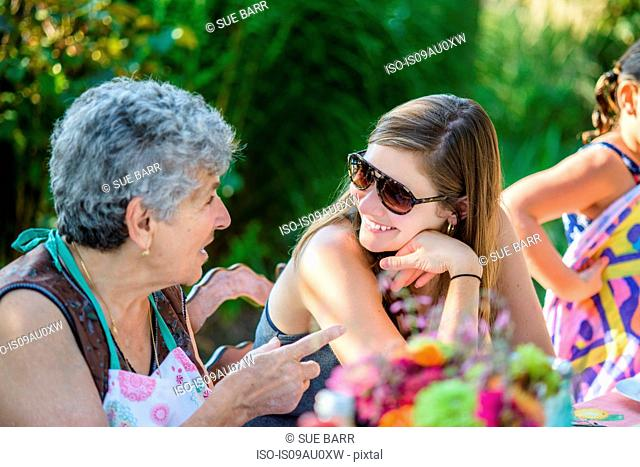 Mid adult woman talking to senior woman in garden