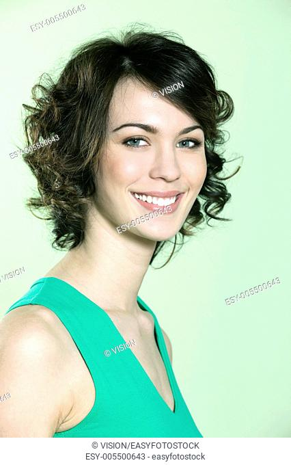studio shots portrait of a beautiful caucasian young smiling woman on green background