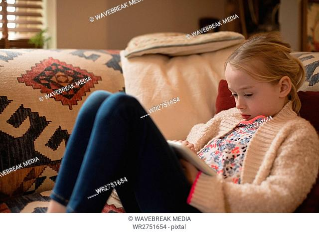 Girl sitting on sofa and using digital tablet in living room