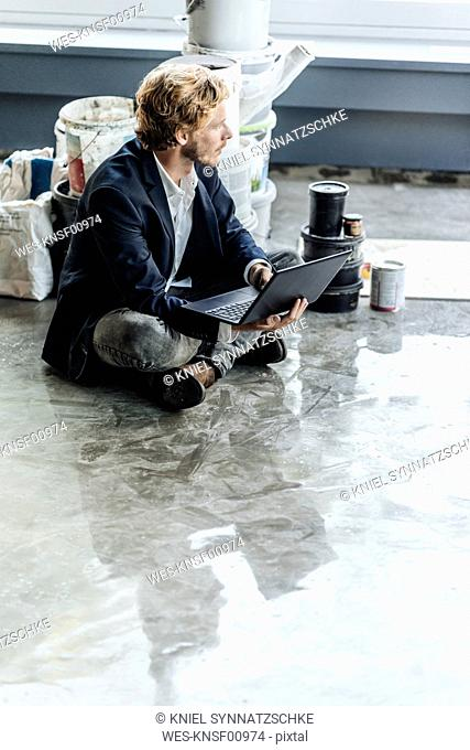 Businessman sitting on floor with laptop and paint buckets