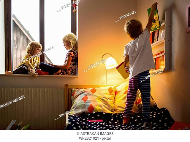 Boy choosing books from shelf with sisters sitting on window sill at home