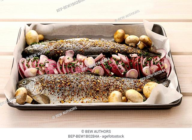 Rainbow trout with onions before baking. Healthy food