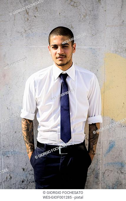 Portrait of young businessman with tattoos on his forearms