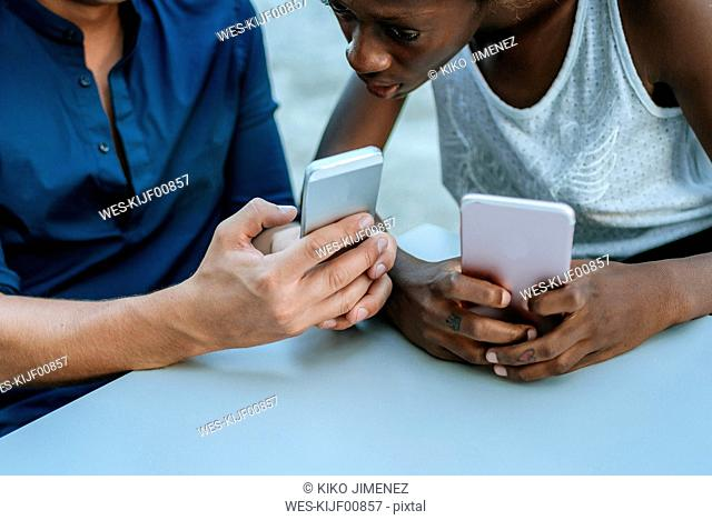 Close-up of young couple using smartphone