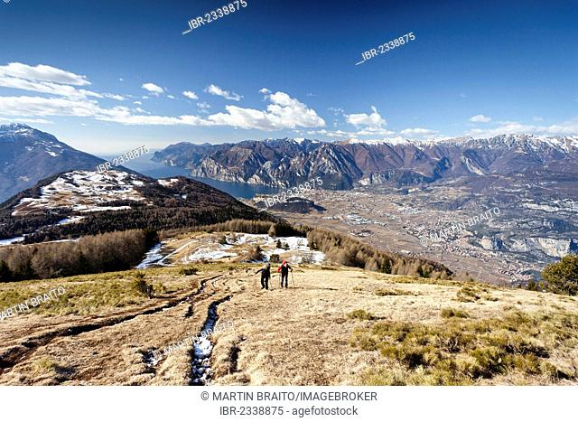 Hikers during the ascent to Monte Stivo above St. Barbara, Lake Garda and the village of Riva at the rear, the village of Arco below, Trentino, Italy, Europe