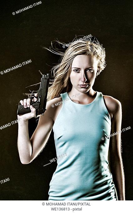 Dangerous young woman holding a gun